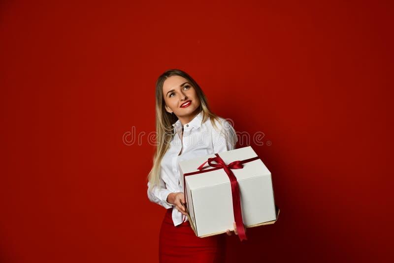 Het jonge de gift van de de greep witte doos van de blondevrouw huidige glimlachen probeert om het op de viering van de Verjaarda royalty-vrije stock foto