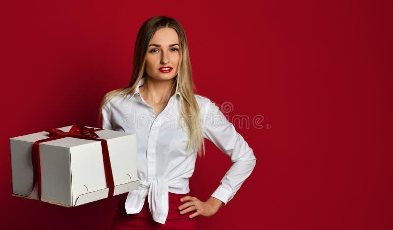 Het jonge de gift van de de greep witte doos van de blondevrouw huidige glimlachen probeert om het op de viering van de Verjaarda royalty-vrije stock foto's
