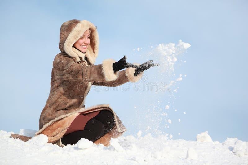 Het jonge de vrouwen hurken en handen werpen sneeuw stock foto's