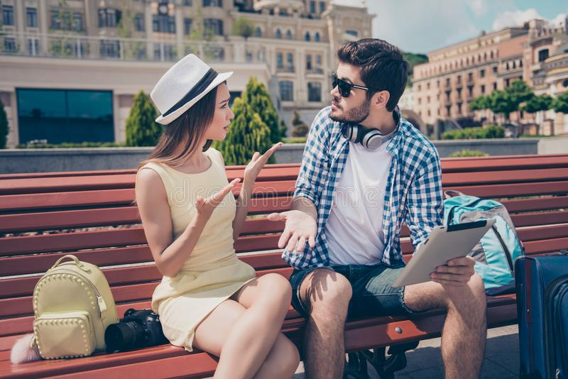 Het jonge die echtpaar werd op vakantie in stad wordt verloren De gefrustreerde dame debatteert met haar vriend, die pda, heeft g stock afbeeldingen
