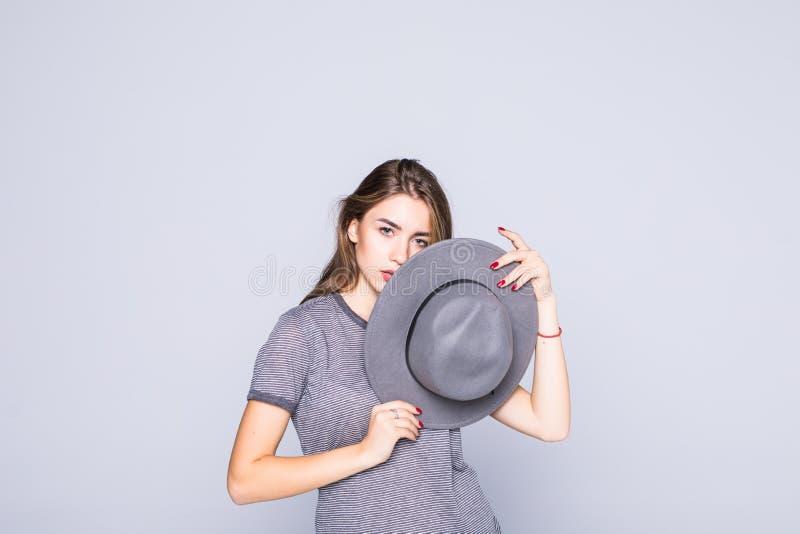 Het jonge die gezicht van de vrouwendekking met de zomerhoed op witte achtergrond wordt ge?soleerd royalty-vrije stock foto's