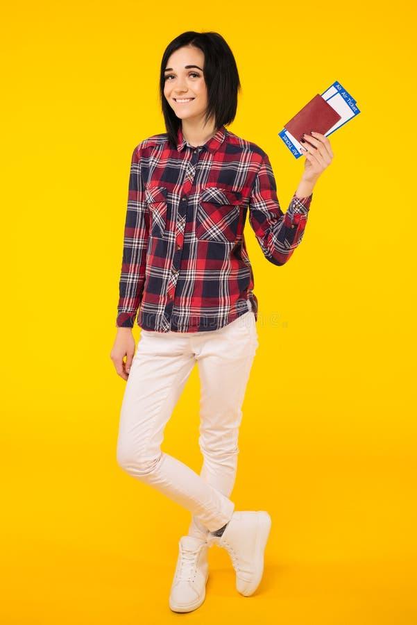 Het jonge die glimlachen wekte het kaartje van de het paspoort instapkaart van de studenteholding op gele achtergrond wordt geïso stock afbeeldingen