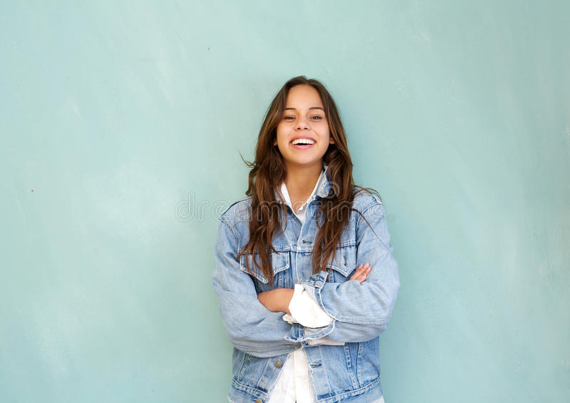 Het jonge die vrouw lachen met wapens in ontspannen worden gekruist stelt tegen blauwe achtergrond stock fotografie