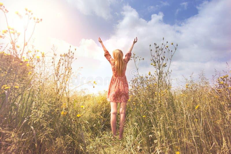 Het jonge die vrouw ontspannen met wapens aan de hemel in het midden van de aard worden opgeheven stock afbeeldingen