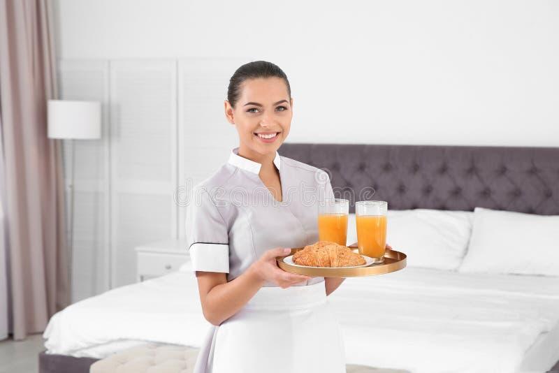 Het jonge dienblad van de kamermeisjeholding met ontbijt royalty-vrije stock foto
