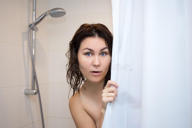 Het jonge doen schrikken vrouw verbergen achter douchegordijn stock foto