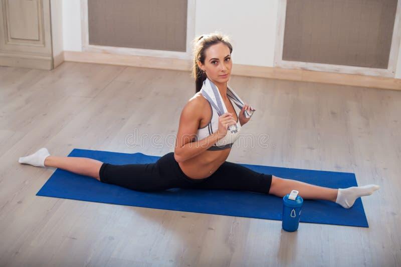 Het jonge donker-haired atletische sportieve slanke vrouw doen stock afbeelding