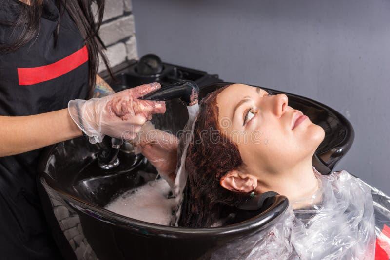 Het jonge donkerbruine haar van de kapperwas van vrouwelijke cliënt met dy royalty-vrije stock foto