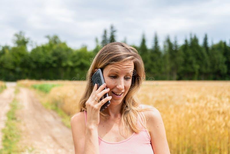 Het jonge donkerbruine lopen in aard die op haar mobiele telefoon spreken stock afbeelding
