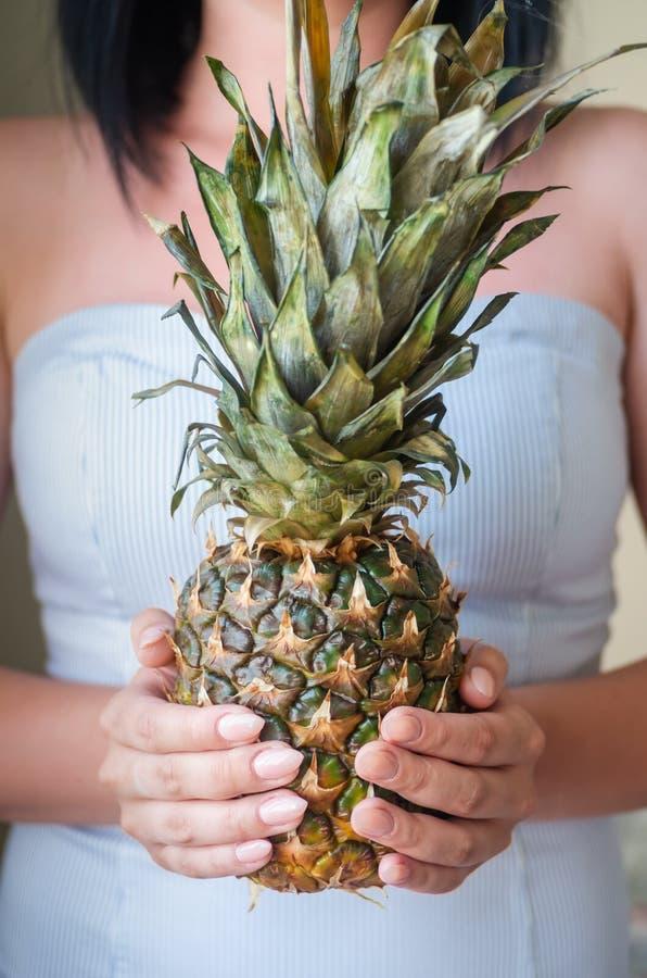 Het jonge donkerbruine meisje houdt rijpe ananas in haar handen stock afbeeldingen