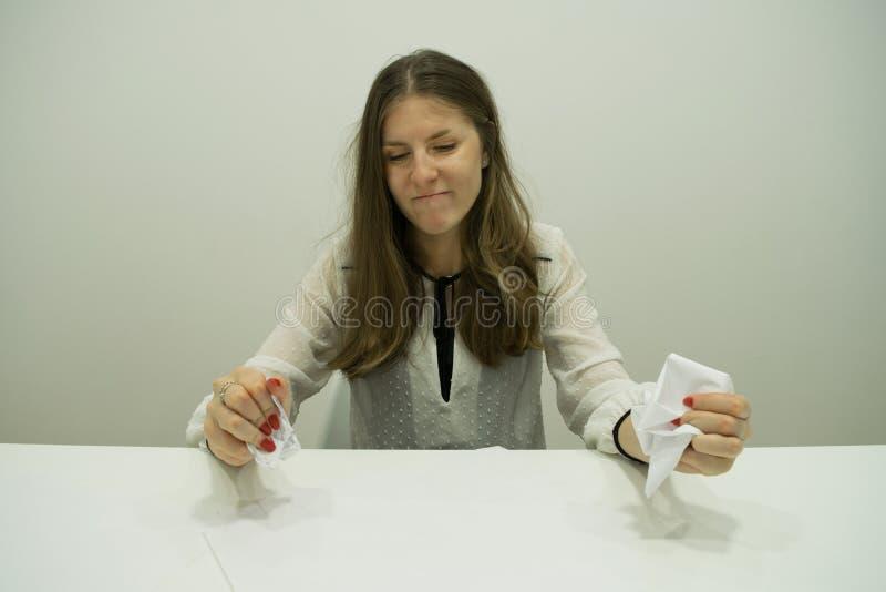 het jonge donkerbruine meisje met stromend haar zit bij een lijst met documenten royalty-vrije stock foto