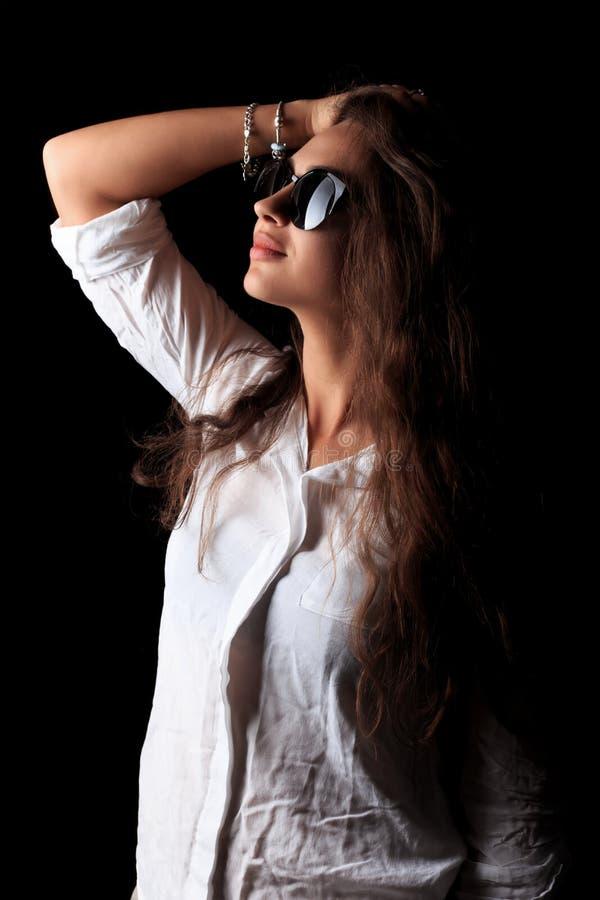 Het jonge donkere vrouw stellen op de camera in zwarte zonnebril in het rustige licht stock fotografie