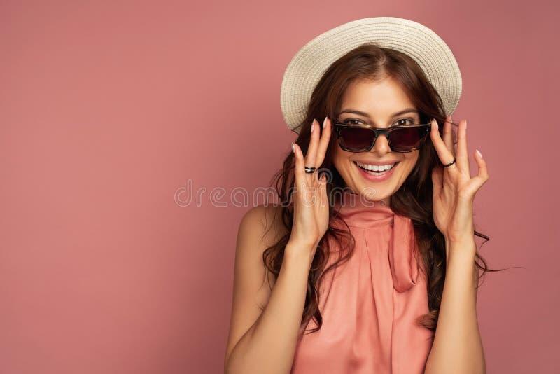 Het jonge donkerharige met strohoed glimlacht ruim bij de camera kijkend door haar zonnebril, roze achtergrond royalty-vrije stock afbeeldingen