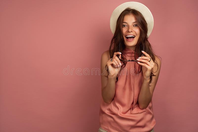 Het jonge donkerharige met strohoed lacht oprecht bij de camera houdend haar zonnebril, roze achtergrond stock afbeelding