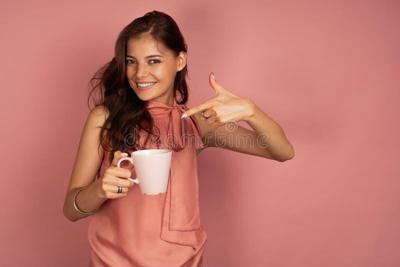 Het jonge donkerharige richt op haar kop glimlachend bij de camera, roze achtergrond royalty-vrije stock foto