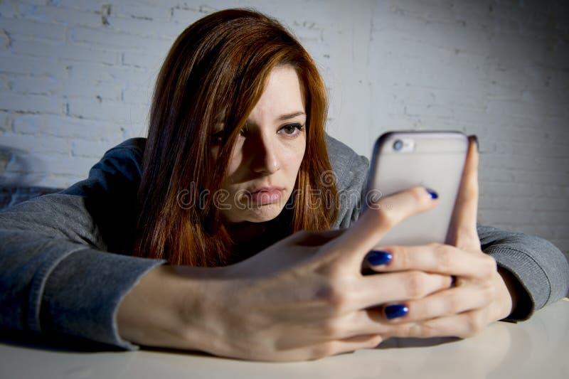 Het jonge droevige kwetsbare meisje die mobiele telefoon met behulp van deed schrikken en het wanhopige lijdende online misbruik  stock fotografie