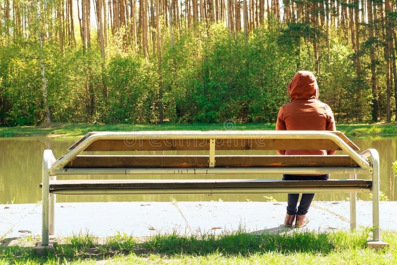 Het jonge droevige meisje en zit op een houten bank in het Park, werd zij teleurgesteld door de zoete liefde Dromen van de toekom stock foto's