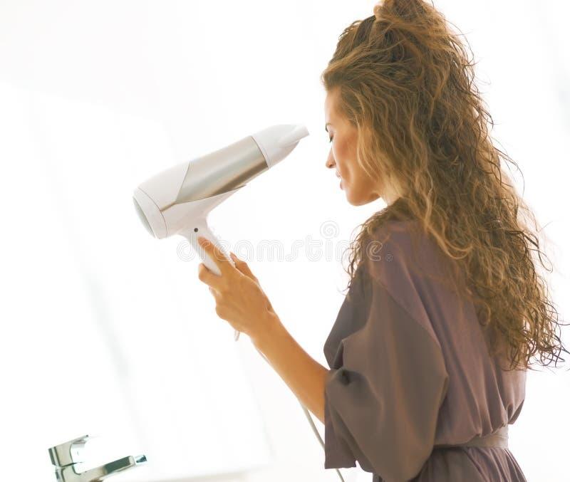 Het jonge drogende haar van de vrouwenslag in badkamers stock afbeelding