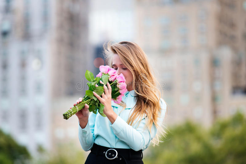 Het jonge elegante mooie vrouw roze ruiken nam bloemen toe stock fotografie