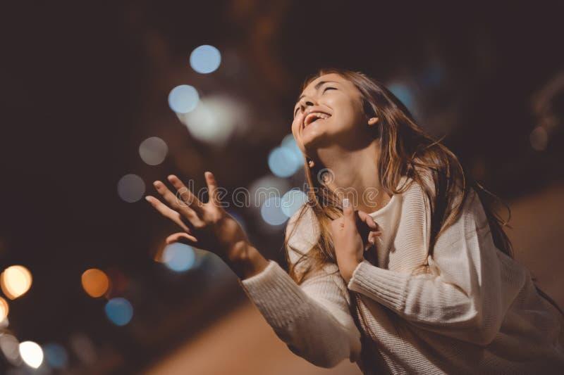 Het jonge emotionele beklemtoonde vrouw gillen die, stadsstraat in de nacht, het gelijk maken steekt in openlucht bokeh achtergro stock afbeelding