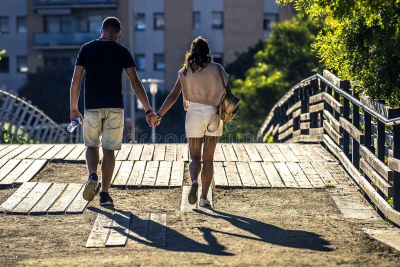 Het jonge en aantrekkelijke paar gaat langs de brug in park royalty-vrije stock foto