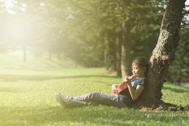 Het jonge en gelukkige Aziatische meisje spelen met ukelelegitaar bij het park in zonnige ochtend stock afbeelding