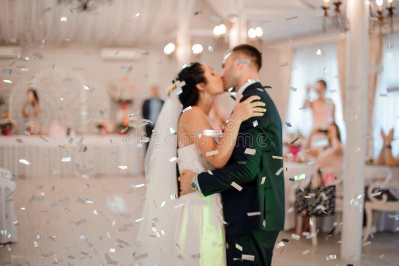 Het jonge en gelukkige echtpaar kussen in het centrum van de restaurantzaal stock afbeeldingen