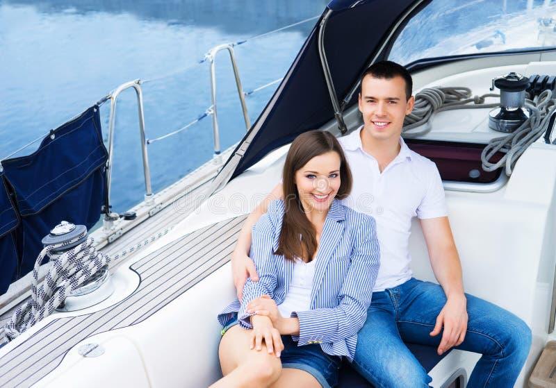Het jonge en gelukkige paar ontspannen op een boot stock foto