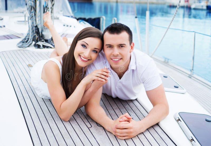 Het jonge en gelukkige paar ontspannen op een boot royalty-vrije stock foto's