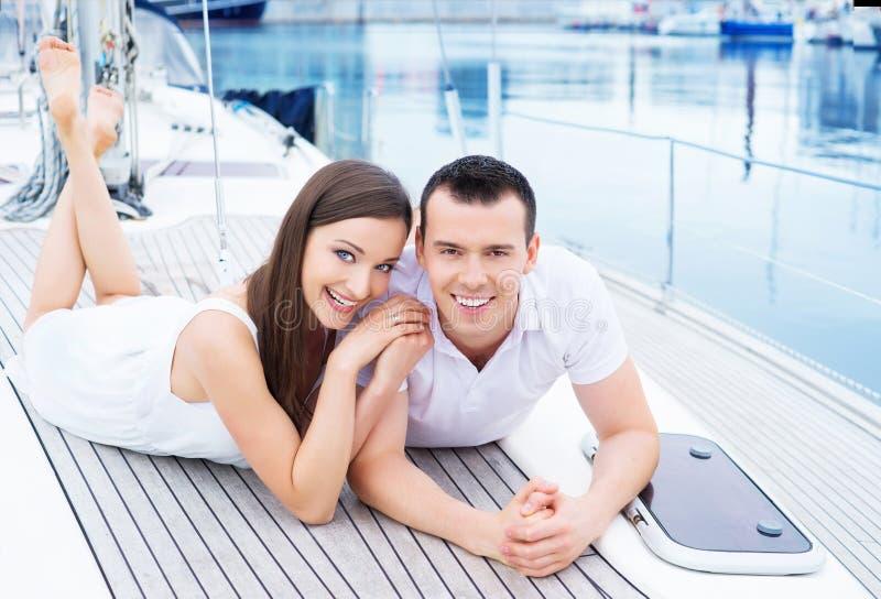 Het jonge en gelukkige paar ontspannen op een boot stock afbeelding