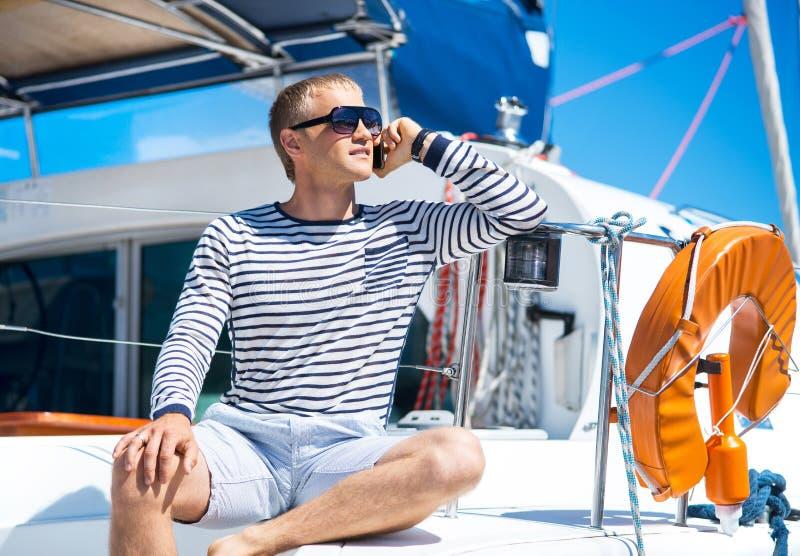 Het jonge en knappe mens ontspannen op een varende boot royalty-vrije stock foto