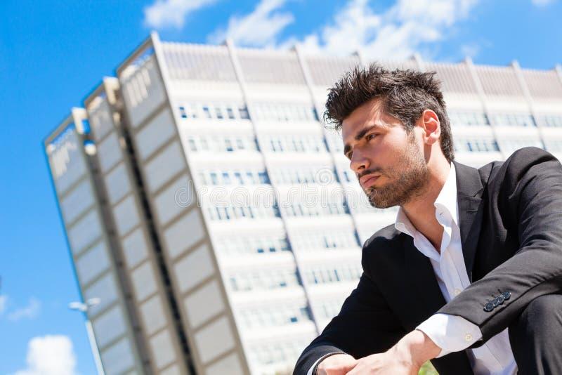 Het jonge en knappe zakenmanzitting denken stock foto's