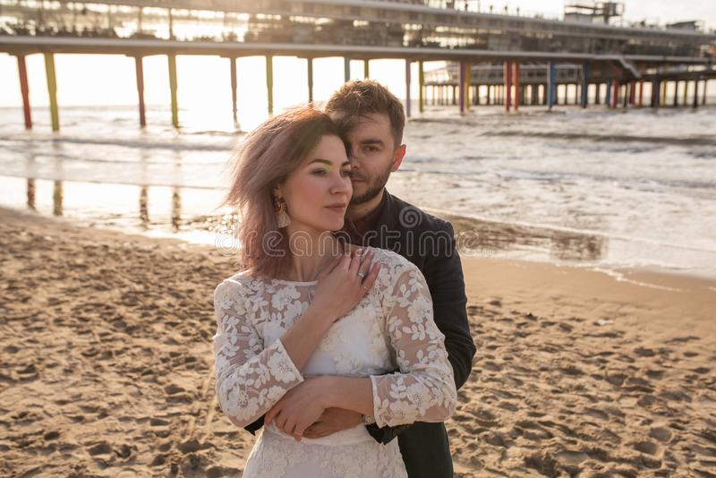 Het jonge en mooie echtpaar in greep viert hun huwelijk tijdens zonsondergang op strand stock afbeelding