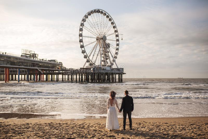 Het jonge en mooie echtpaar viert hun huwelijk tijdens zonsondergang op strand stock foto's