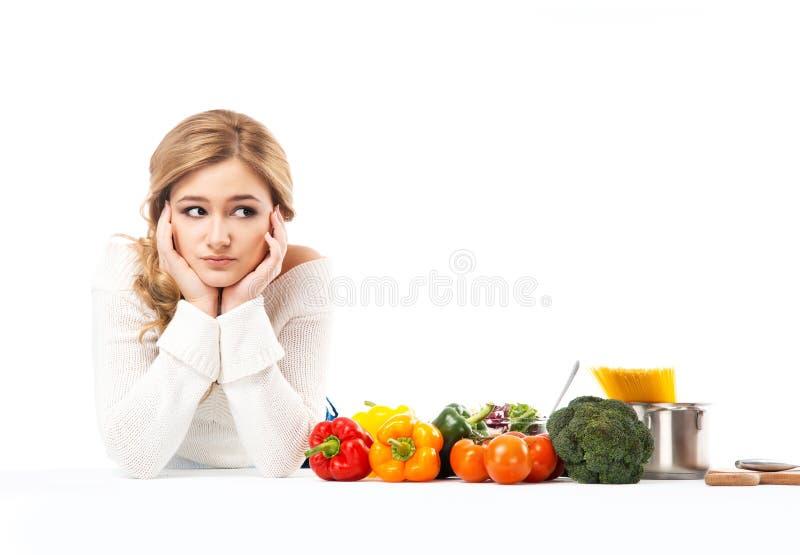 Het jonge en mooie huisvrouwenvrouw koken in een keuken stock foto