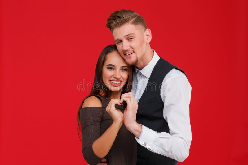 Het jonge en mooie paar in liefde maakt een hart op een rode achtergrond Het concept de Dag van Valentine ` s royalty-vrije stock foto