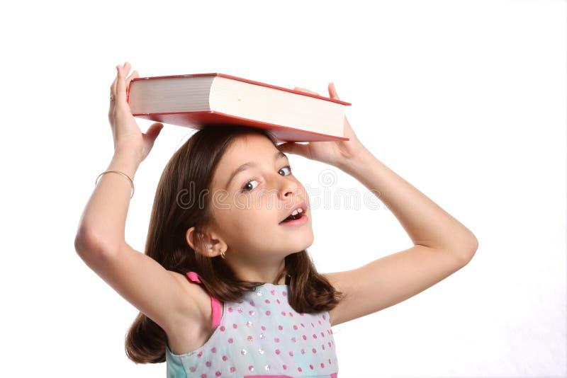 Het jonge in evenwicht brengende boek van het Meisje op hoofd stock foto's