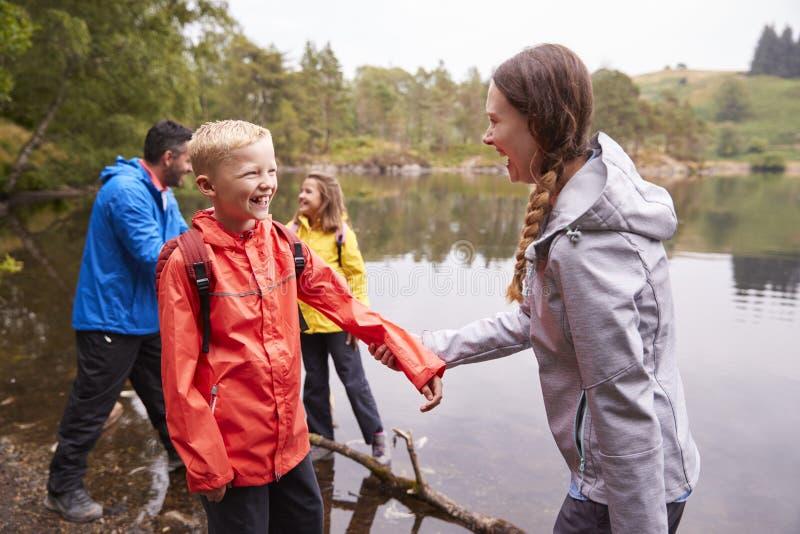 Het jonge familie spelen met hun kinderen op de kust van een meer, sluit omhoog, Meerdistrict, het UK royalty-vrije stock foto