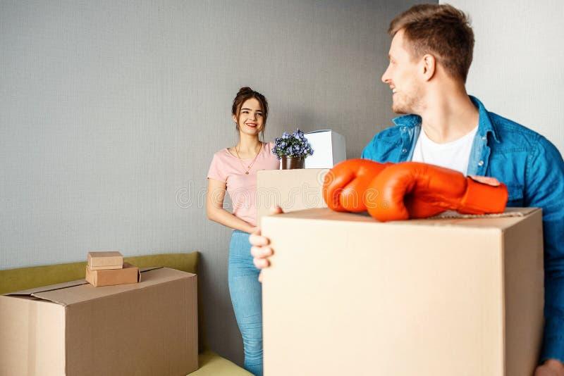 Het jonge familiepaar kocht of huurde hun eerste flatje De gelukkige mooie mensen dragen dozen met materiaal en bekijken bij royalty-vrije stock afbeeldingen