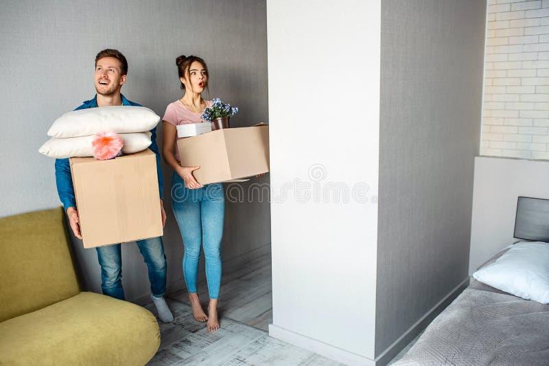 Het jonge familiepaar kocht of huurde hun eerste flatje De mooie mensen gaan ruimte in en dragen dozen met materiaal stock foto