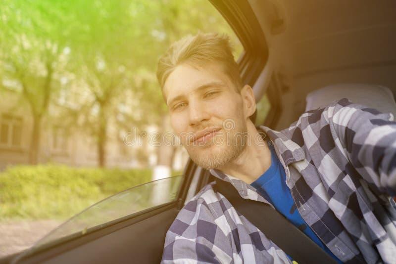Het jonge gebaarde mannetje neemt een zelfportret van zich zitting op de voorautozetels stock foto
