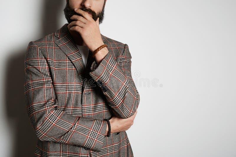 Het jonge gebaarde zakenmanmodel stelt in toevallig jasje en leeg wit de zomerkatoen van de t-shirtpremie, op wit stock foto