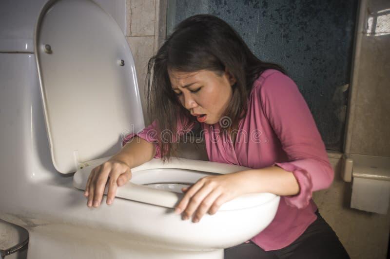 Het jonge gedronken of zwangere Aziatische vrouw braken en het werpen omhoog in toiletwc die onwel en zieke lijdende maag voelen  royalty-vrije stock foto's