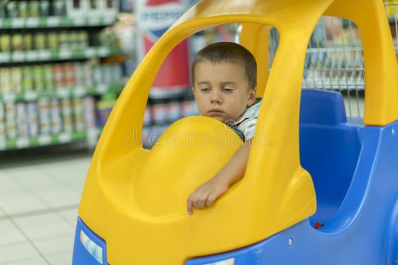 Het jonge geitje is bored in de opslag De slaapjongen is als voorzitter op het karretje in de supermarkt stock foto