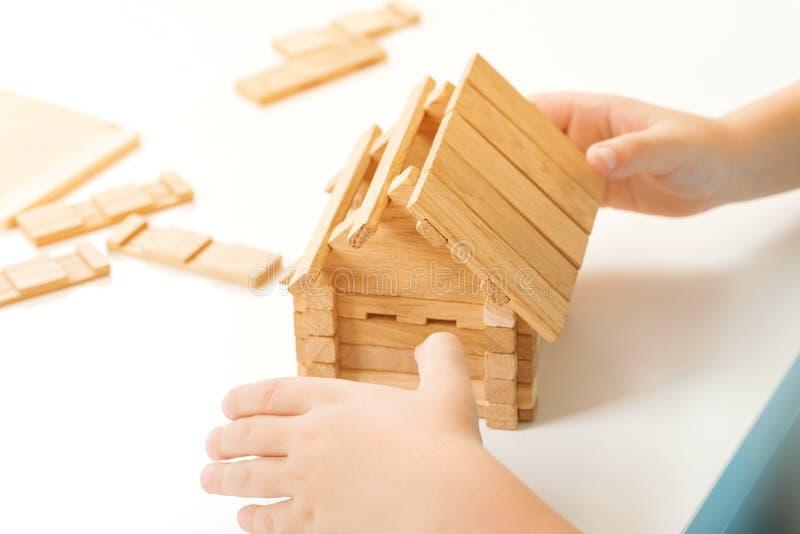 Het jonge geitje bouwt blokhuis, omhoog sluit Kindspelen met houten blokken Plattelandshuisjeminiatuur Het concept van het famili stock afbeeldingen