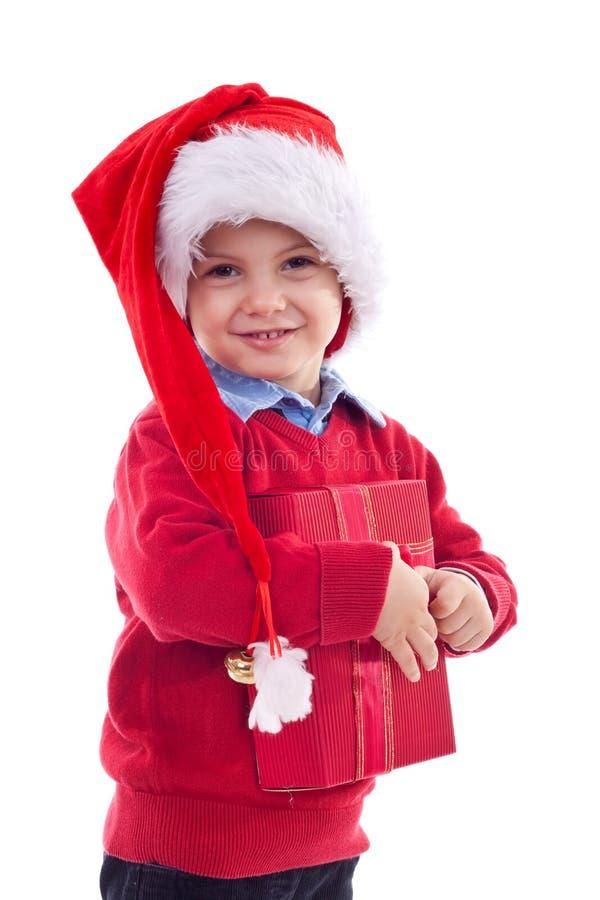 Het jonge geitje dat van de kerstman een heden houdt stock foto's