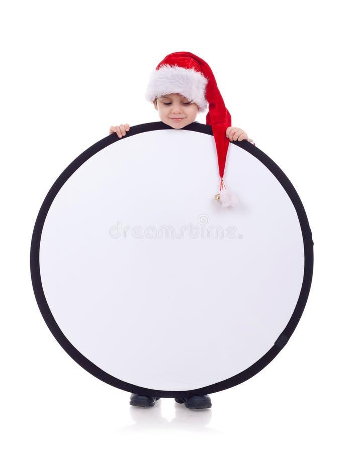 Het jonge geitje dat van de kerstman een teken houdt stock fotografie