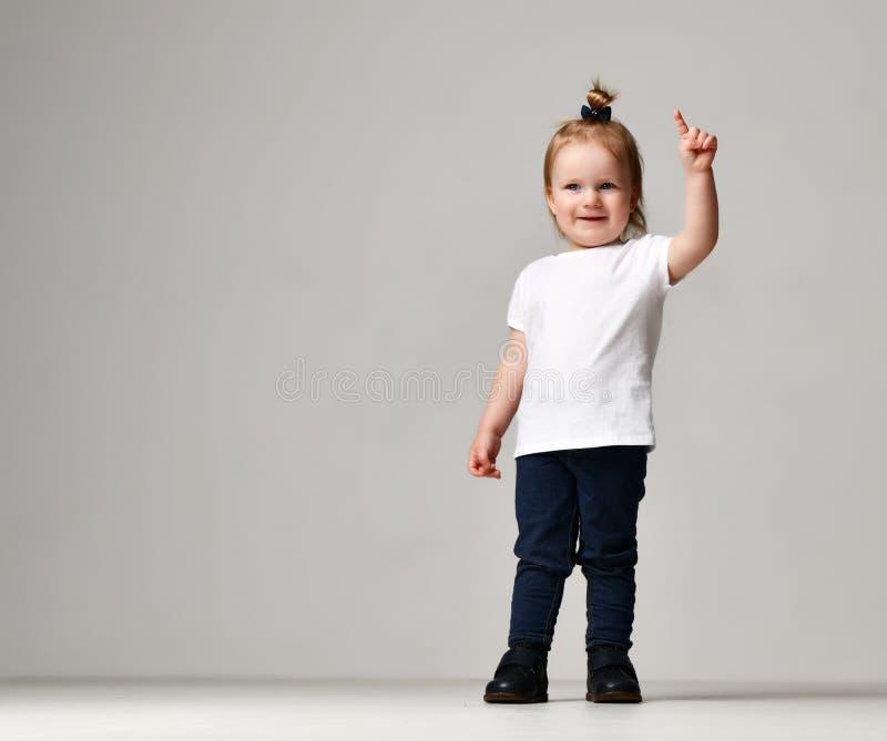 Het jonge geitje die van het de babymeisje van het peuterkind zich in witte vrije tekst ruimtet-shirt bevinden die vinger benadru royalty-vrije stock fotografie