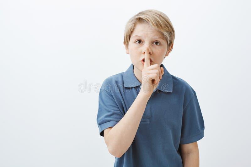 Het jonge geitje die vriend vragen houdt geheim Portret van ernstig leuk blond mannelijk kind die in blauwe t-shirt shh terwijl h stock afbeeldingen