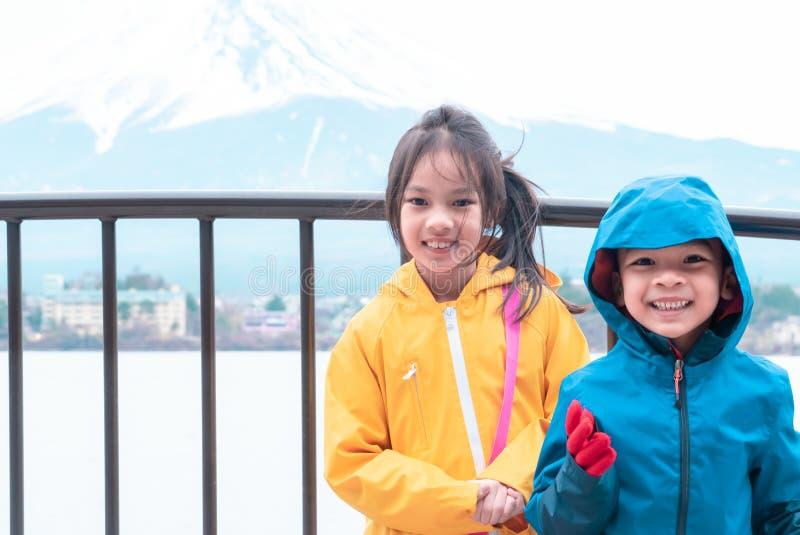 Het jonge geitje die zich voor Kawaguchiko-meer bevinden en zet fuji in de winter op royalty-vrije stock fotografie